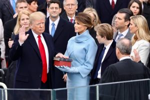 President Donald Trump being sworn in on January 20, 2017 at the U.S. Capitol building in Washington, D.C. Melania Trump wears a sky-blue cashmere Ralph Lauren ensemble. He holds his left hand on two versions of the Bible, one childhood Bible given to him by his mother, along with Abraham Lincoln's Bible. 2017-01-20). Source: https://www.facebook.com/WhiteHouse/photos/a.1199645353456529.1073741828.1191441824276882/1199654763455588/?type=3&theater